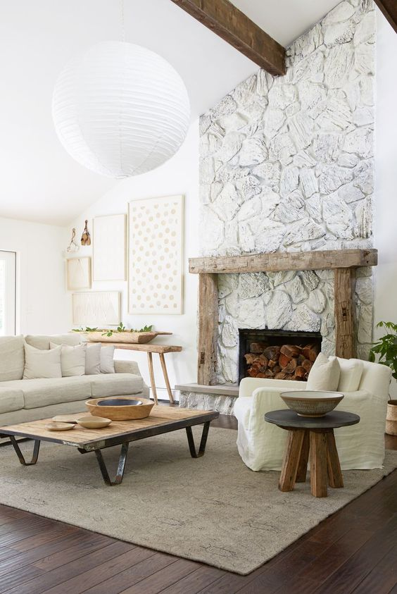 a whitewashed stone fireplace with a rough wood mantel, firewood inside brings a cozy farmhouse feel to the room