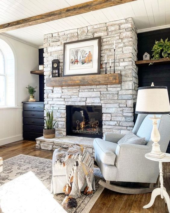 a whitewashed stone fireplace with a rough wooden mantel, vintage decor and a potted plant brings a farmhouse feel
