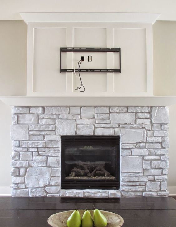 a whitewashed stone fireplace with a white mantel and a built-in fireplace looks very cozy and very natural