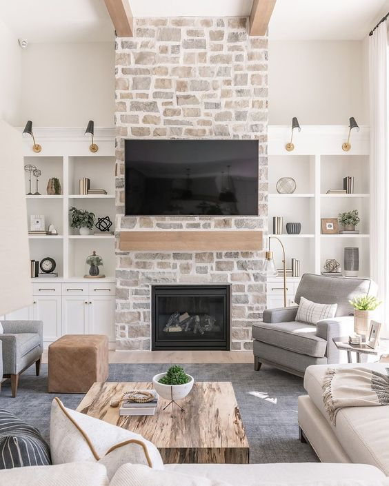 a whitewashed stone fireplace with a wooden mantel and storage units on each side of it is a cozy and chic touch to the room decor