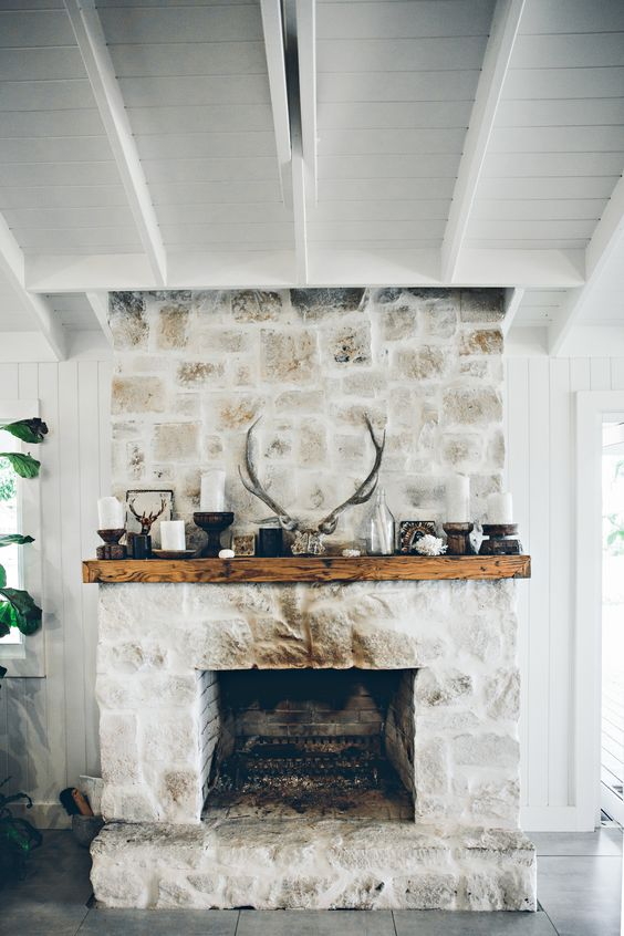 a whitewashed stone fireplace with a wooden mantel with candles, antlers and more rustic decor for a cozy feel