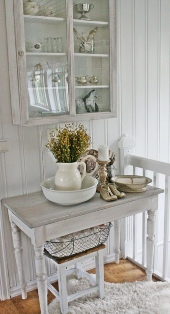 a whitewashed storage cabinet with a glass door and matching furniture items for a small and cozy shabby chic nook