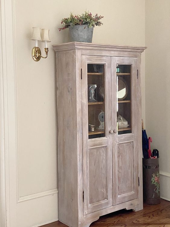 a whitewashed storage unit with glass doors will be great for displaying and storing anything you want and anywhere you want
