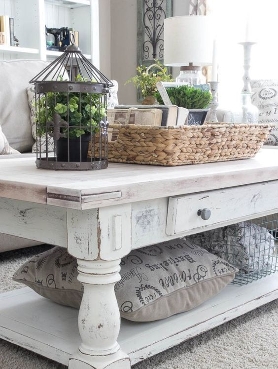 a whitewashed table used as a coffee one, with drawers and an additional open shelf is a functional and refined idea for a farmhouse space
