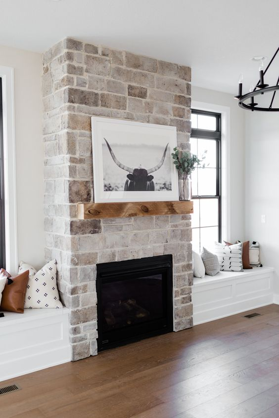 a whitewashed vintage brick fireplace with a mantel with some decor and windowsill seat next to it