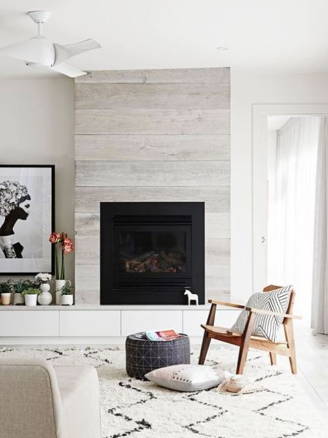 a whitewashed wood clad fireplace perfectly matches a contemporary space and the neutral color scheme applied here