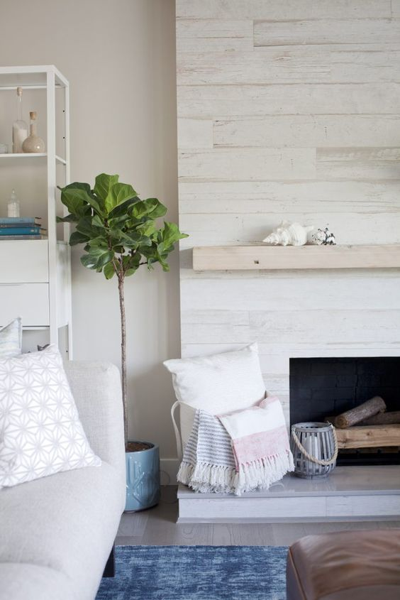 a whitewashed wood fireplace with a neutral mantel, firewood, a basket with pillows looks ethereal and chic