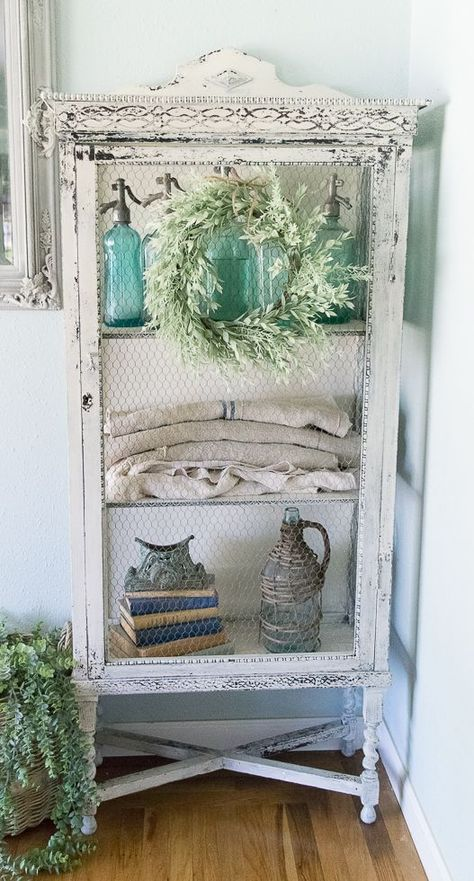 an antique whitewashed farmhouse storage unit with a net door is a beautiful idea for a vintage or shabby chic space