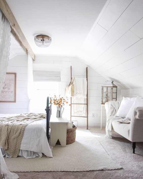 an attic bedroom with whitewashed wooden walls, neutral and cozy furniture, neutral bedding and lace curtains is chic