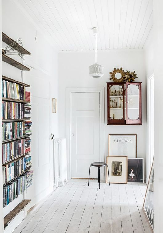 an eclectic entryway with white walls, a whitewashed floor, vintage furniture and a pendant lamp plus artworks