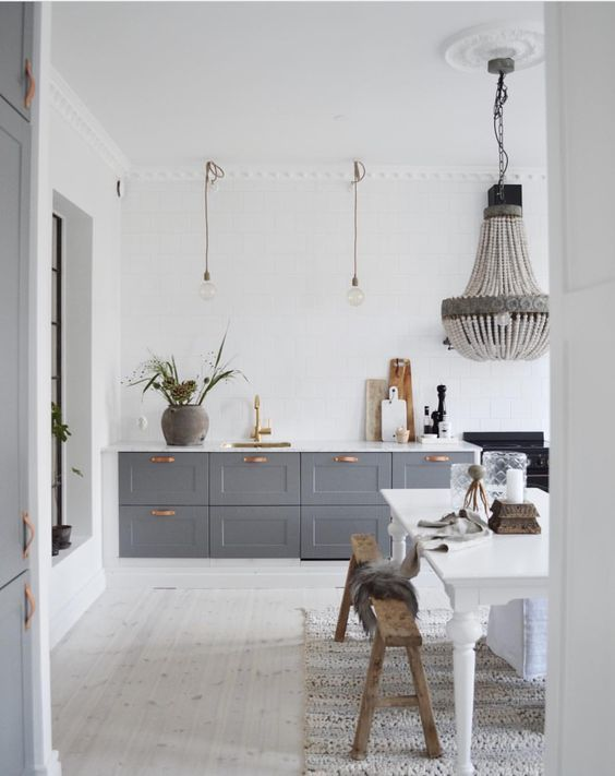 an eclectic kitchen with white walls and a whitewashed floor, grey cabinets, a statement bead chandelier over the dining space