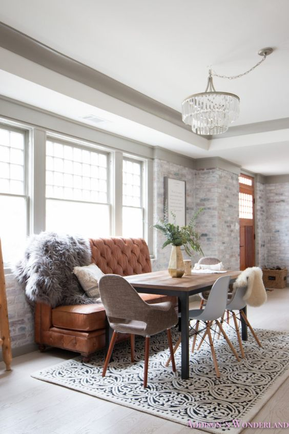 an elegant dining space in farmhouse style, with whitewashed brick walls, a crystal chandelier, a leather sofa and a printed rug
