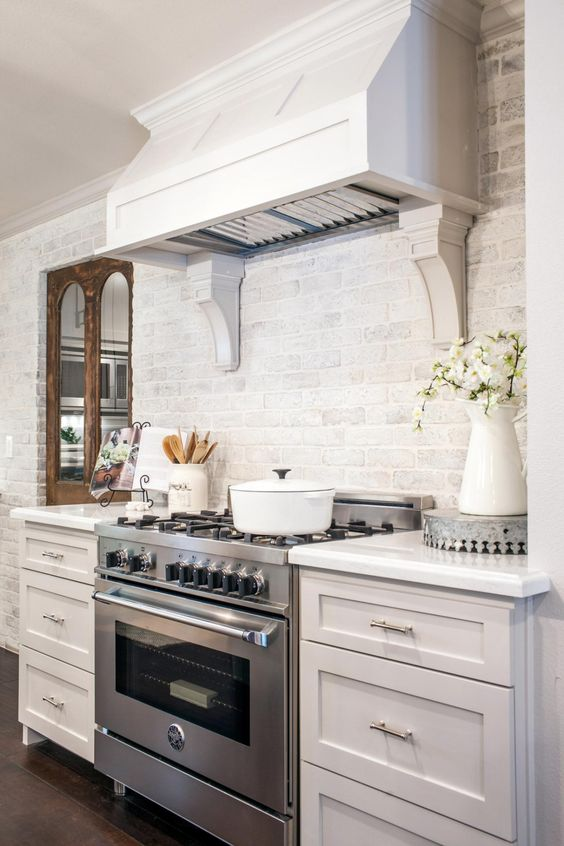 an elegant kitchen with whitewashed brick walls, vintage cabinetry, a large hood looks chic and cool