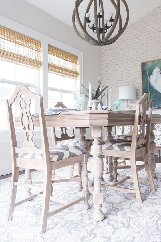 an elegant vintage whitewashed dining table and matching chairs with printed seats are ideal for a farmhouse dining space