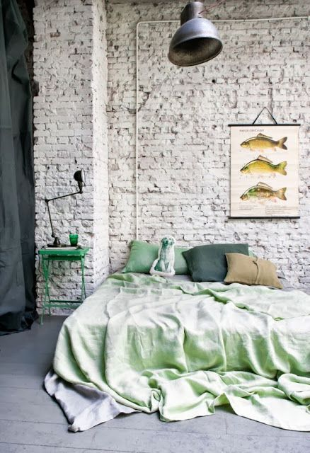 an industrial bedroom with a whitewashed brick wall, a bed with bright bedding, an industrial lamp and a catchy artwork