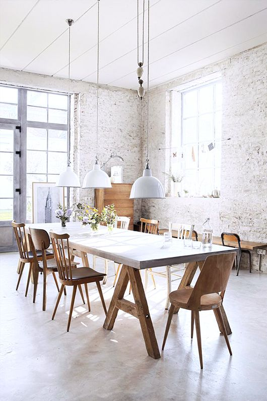 an industrial dining room with whitewashed brick walls, wooden and metal furniture, pendant lamps that highlight the height of the ceiling