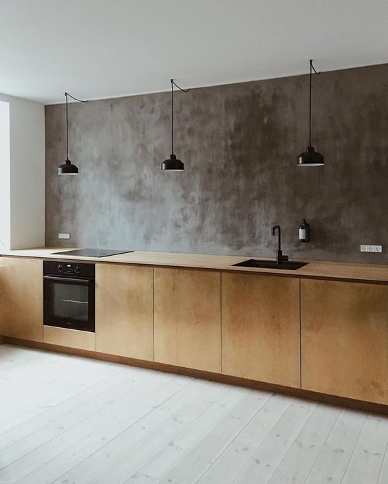 an industrial kitchen with a concrete wall, plywood cabients and a whitewashed floor plus black lamps