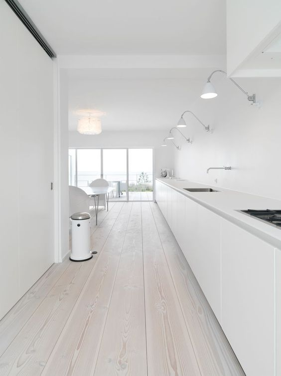 an ultra-minimalist white kitchen with a whitewashed wooden floor that softens the look of the space a bit