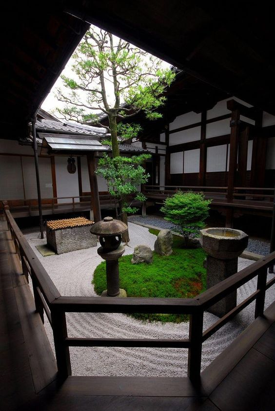 a Japanese courtyard with grass, stone larnterns and a stone water tub, low trees looks very refreshing