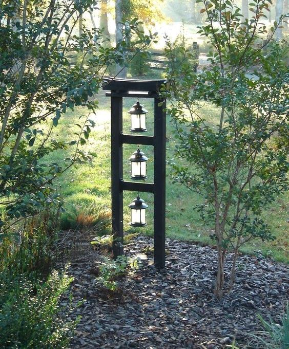 a Japanese front yard with pebbles, some thin trees and a stand with lanterns is a lovely idea to apply to your outdoor space
