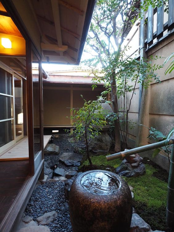 a beautiful Japanese backyard with pebbles and rocks, some moss, a couple of trees and a traditional bamboo fountain in the center