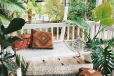 a boho front porch with a rug, a hammock, lots of lanterns hanging, potted plants and candles around