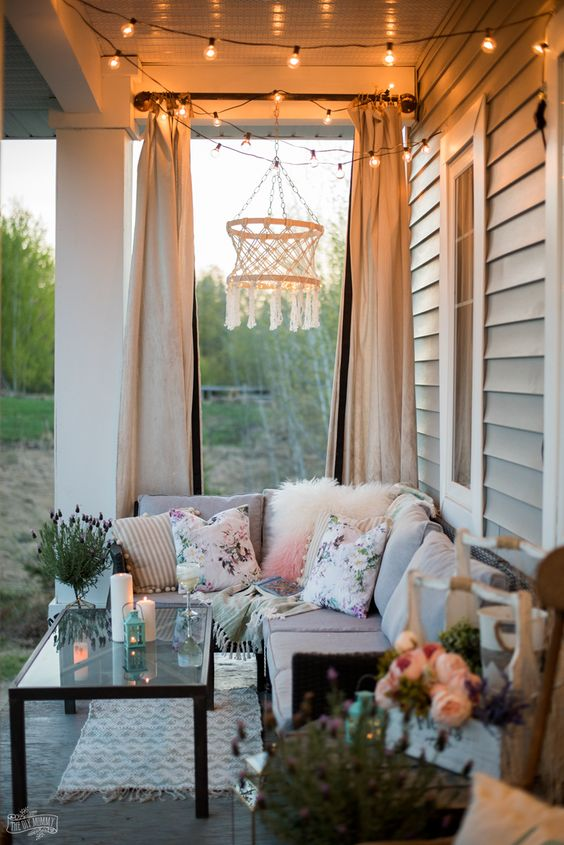 a boho summer porch with a neutral sectional sofa, bright printed pillows, a macrame chandelier, a glass coffee table and candles