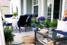 a bold boho summer porch with navy furniture, a printed rug, jute ottomans, a glass coffee table and lots of potted greenery