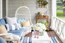 a bright and welcoming summer porch with rattan furniture, a wall garden, a hanging chair and some blue textiles