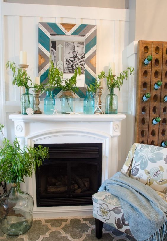 a bright summer mantel with a chevron mirror frame, blue jars with greenery arrangements, starfish and seashells