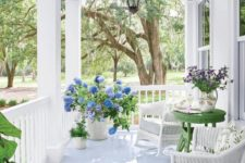 a bright summer porch done in white with touches of juicy green, blooms, lanterns and wicker furniture