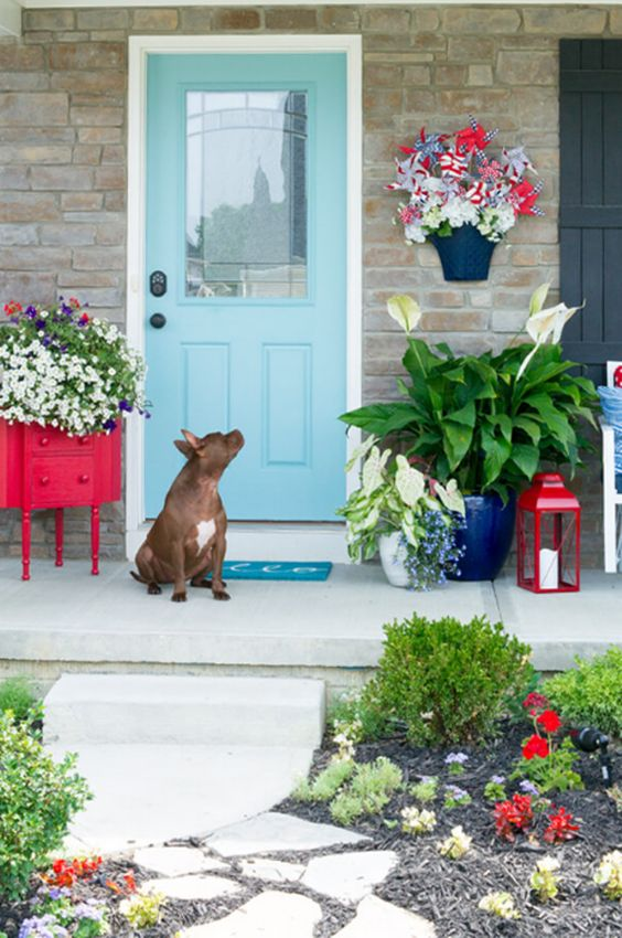 a bright summer porch with a sideboard turned in a planter, bright potted blooms and a red candle lantern
