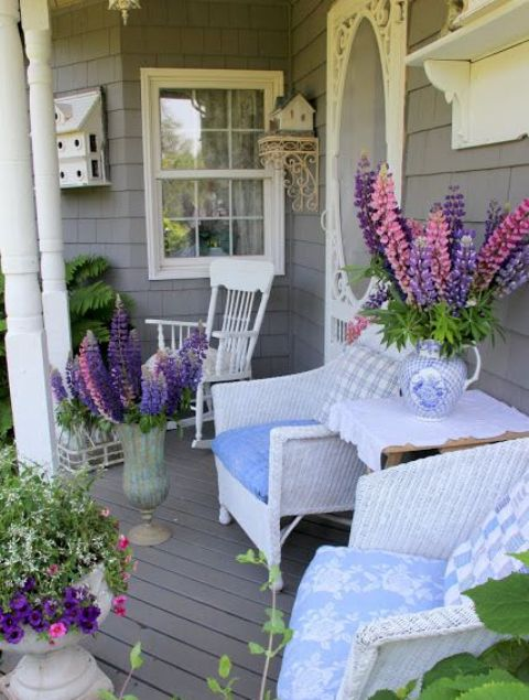a bright summer porch with white furniture and super colorful blooms in pots and urns