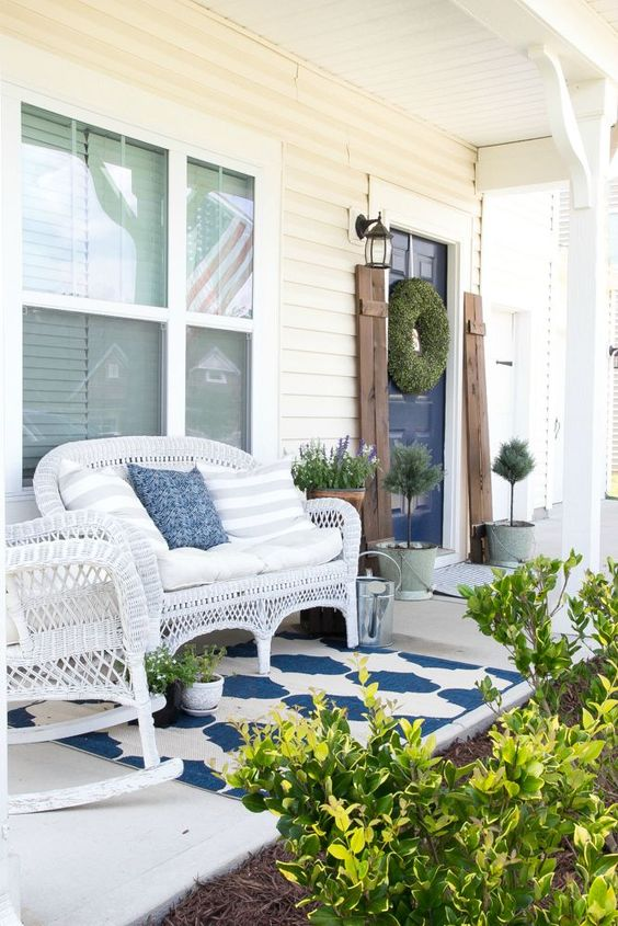 a bright summer porch with white wicker furniture, potted greenery and blooms and a printed rug