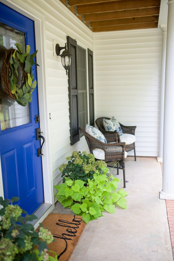 a bright summer porch with wicker furniture, shutters, a rug, potted greenery and floral pillows