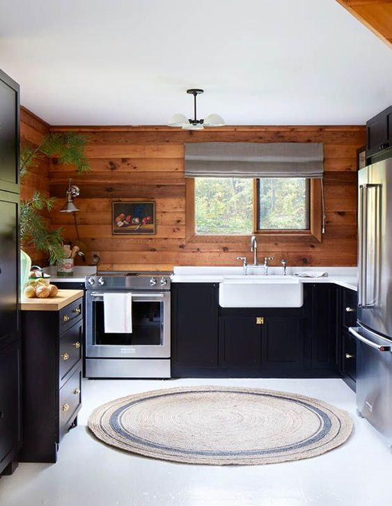 a cabin kitchen clad with stained wood, with dark cabinets, wooden and stone countertops