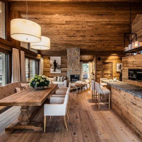 a chalet space fully clad with wood, with wooden cabinets, stone countertops and pendant lamps and candles