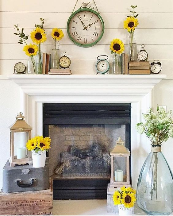 a cheerful summer mantel with sunflowers, vintage clocks, vintage books and candle lanterns around