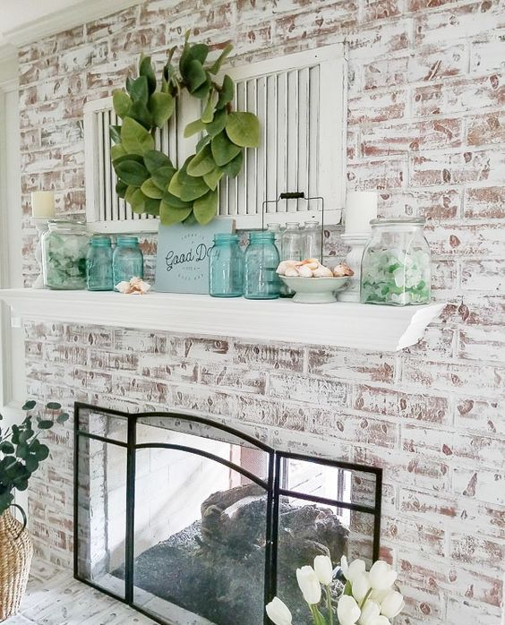 a chic beach farmhouse mantel with blue jars, a greenery wreath, shutters, seashells in bowls