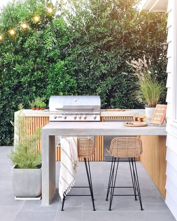 a chic contemporary bbq area of wood and concrete, with a grill and a cooking zone, a concrete dining area and rattan stools