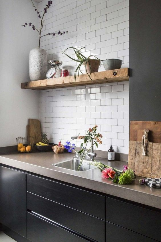a chic kitchen with sleek black cabinets, open shelves, a white subway tile backsplash and concrete countertops