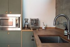 a chic minimalist green kitchen with dark stained wooden countertops and no handles is a bold and cool space with a moody feel