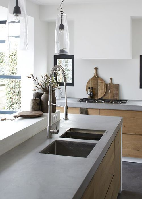 a chic minimalist kitchen with sleek wooden cabinets, concrete countertops, white walls and pendant lamps