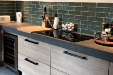a chic modern kitchen with sleek wooden cabinets, a concrete countertop and a grene tile backsplash