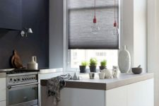 a chic monochromatic minimalist kitchen with concrete countertops and bulbs on red cords
