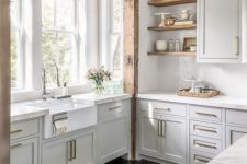 a chic off-white kitchen with neutral stone countertops, gold hardware and rough wooden beams