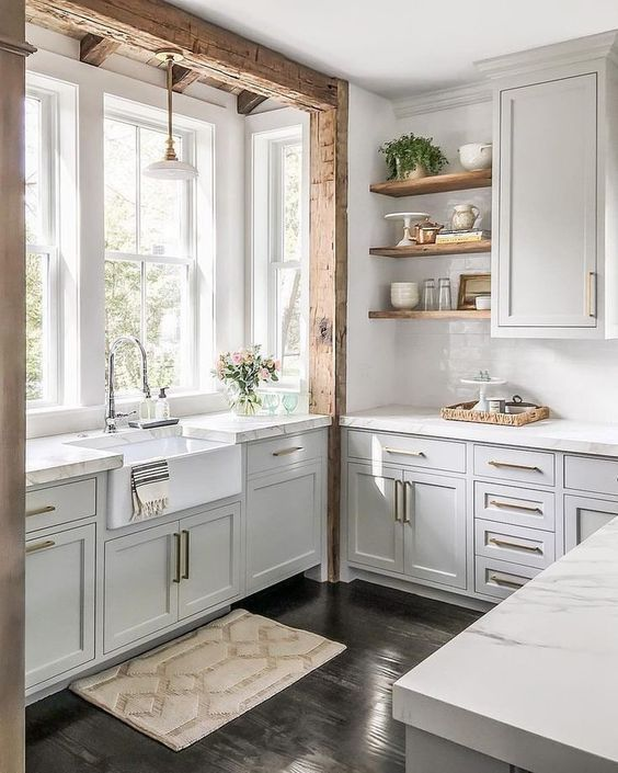 a chic off white kitchen with neutral stone countertops, gold hardware and rough wooden beams