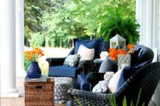 a chic summer porch with navy wicker chairs, a wicker ottoman, potted blooms and greenery and candle lanterns