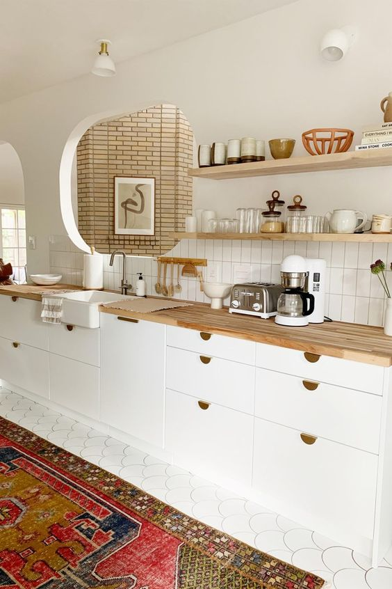 a chic white contemporary kitchen with light stained butcherblock countertops and gold touches looks elegant