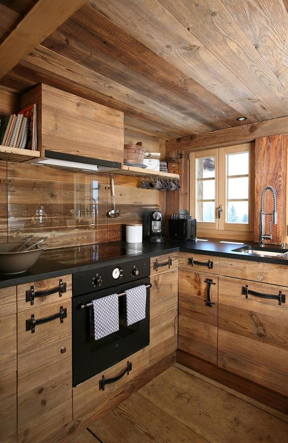 a contemporary chalet kitchen fully done with light stained wood, with a glass backsplash and black leather handles
